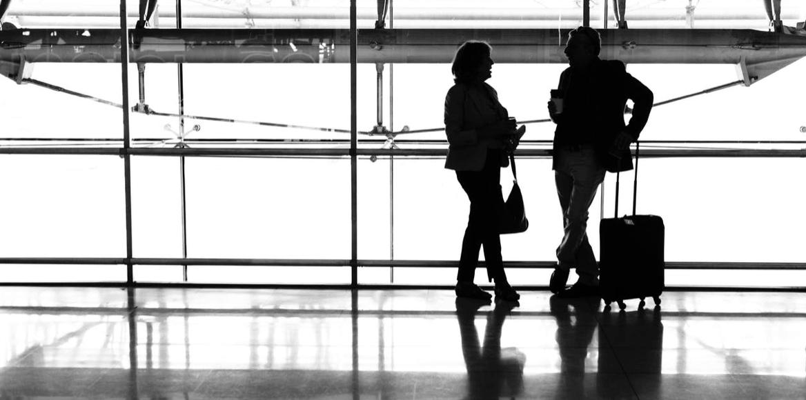 Dve siluety ľudí vedľa seba s batožinou